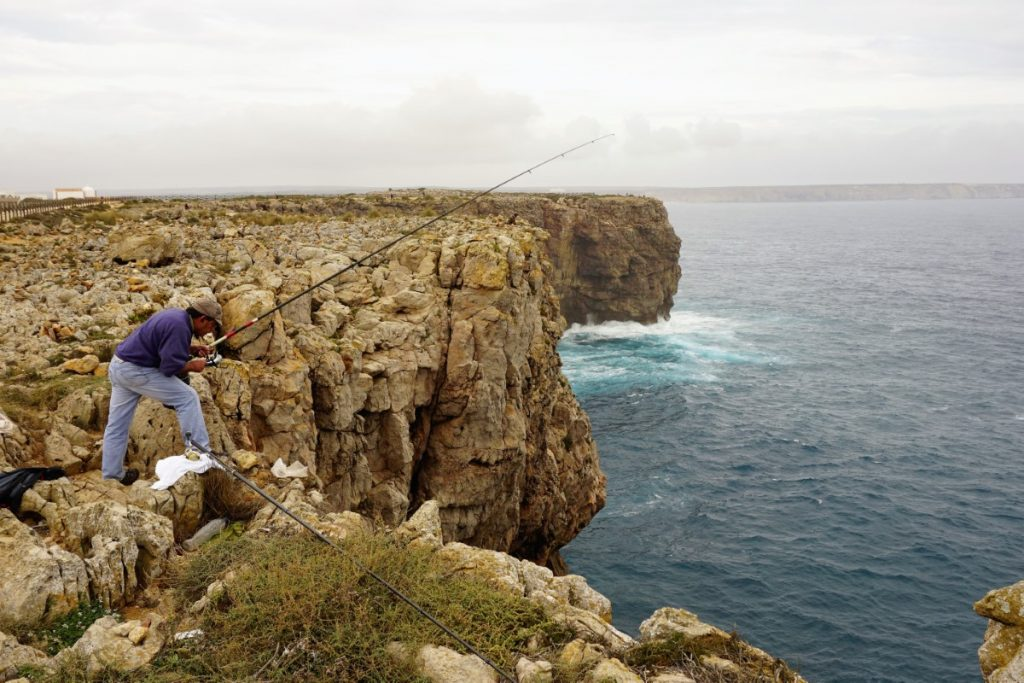 Fisherman on the rocks, in Sagres, along the rugged cliff tops, alongside the Atlantic.